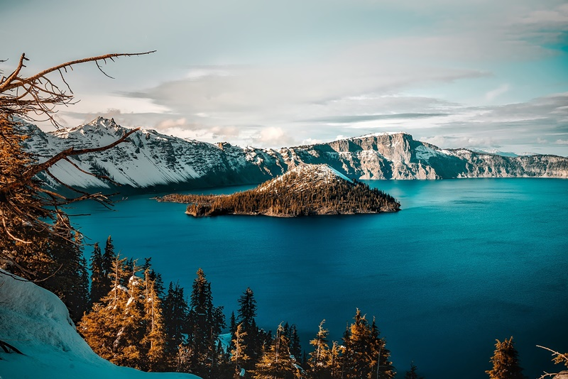 crater lake surrounded by snow covered mountains