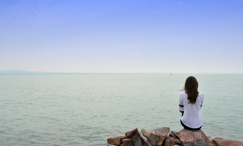 Lady with brown hair sitting on rocks at shore of large Lake Balaton looking at ship in far distance under blue cloudless sky